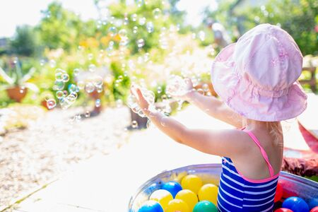 Adorable blonde baby girl 3 year old in a pink hat and blue stripped swimsuit having bath at backyard and playing with bubbles. Summer holiday Stock fotó - 133473188