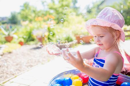 Adorable blonde baby girl 3 year old in a pink hat and blue stripped swimsuit having bath at backyard and playing with bubbles. Summer holiday Stock fotó - 133473187