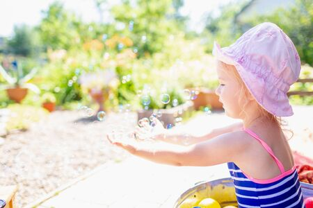 Adorable blonde baby girl 3 year old in a pink hat and blue stripped swimsuit having bath at backyard and playing with bubbles. 写真素材