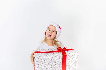 Little smiling girl in santa helper hat holding white gift with red ribbon on white isolated background. Christmas, winter, happiness concept. 写真素材