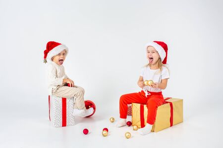 Funny little kids in Santa hat sitting on gift boxes and show their tongues. Isolated on white background. 写真素材