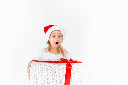 Little smiling girl in santa helper hat holding white gift with red ribbon on white isolated background.