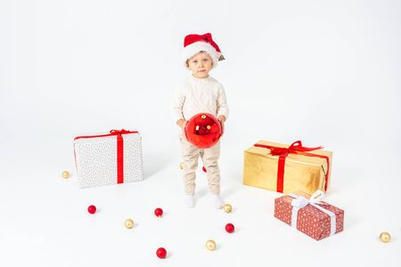 Little boy standing between gifts and holding big red Christmas ball in hands. Isolated on white background.