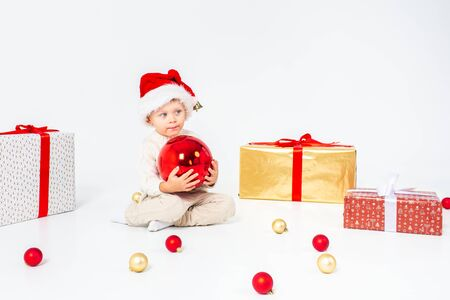 Little boy in Santas hat sitting between gifts and holding big red Christmas ball in hands. Isolated on white background.