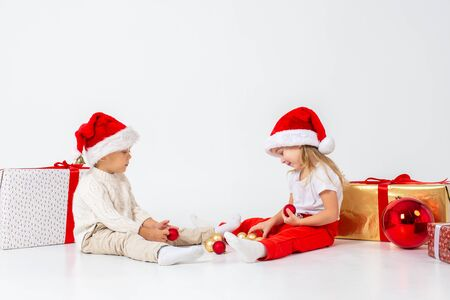 Funny little kids in Santa hat sitting between gift boxes and playing with christmas balls.