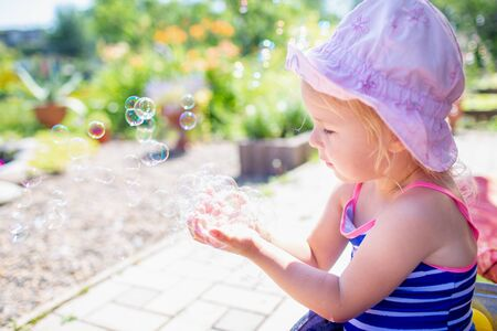 Adorable blonde baby girl 3 year old in a pink hat and blue stripped swimsuit having bath at backyard and playing with bubbles. Summer holiday