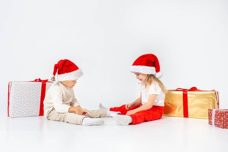Funny little kids in Santa hat sitting between gift boxes and playing with christmas balls. Isolated on white background. New year. 写真素材