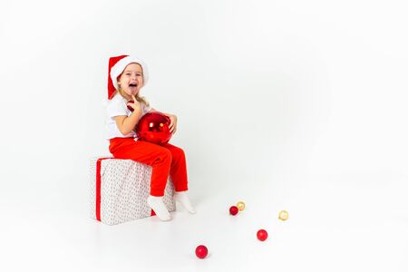 Little girl in santa hat sitting on a giftbox with red ribbon, holding red christmas ball and showing her tongue, white isolated background. Christmas, winter, happiness concept.