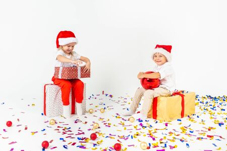 Two funny little kids in Santa hat sitting on gift boxes. Isolated on white background, confetti on a floor. Christmas and new year concept 写真素材