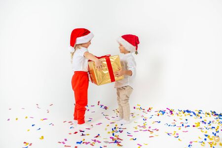 Happy smiling little kids in Santa hat holding big gift box. Isolated on white background. Sale, holidays, christmas, new year, x-mas concept.