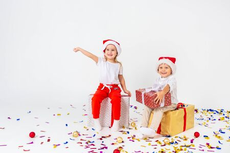 Two funny little kids in Santa hat sitting on gift boxes. Isolated on white background, confetti on a floor. Christmas and new year concept.