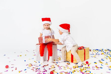 Two funny little kids in Santa hat sitting on gift boxes. Isolated on white background, confetti on a floor. A boy gives a girl a gift. Christmas and new year concept