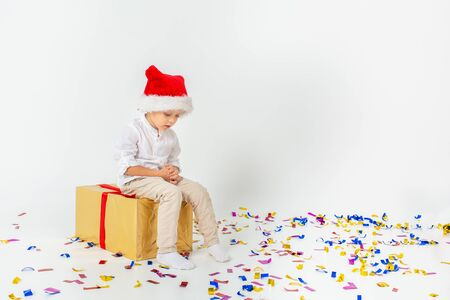 Little sad boy in santa helper hat sitting on a giftbox with red ribbon, white isolated background. Christmas, winter, new year concept. Stockfoto