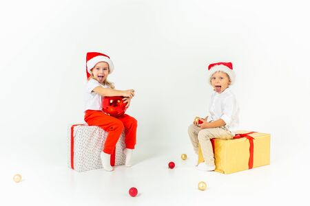 Funny little kids in Santa hat sitting on gift boxes and show their tongues. Isolated on white background.Christmas and new year concept
