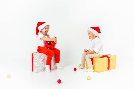 Two funny little kids in Santa hat sitting on gift boxes. Isolated on white background. Christmas and new year concept 写真素材