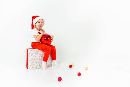 Little girl in santa hat sitting on a giftbox with red ribbon, holding red christmas ball and showing her tongue, white isolated background. Christmas, winter, happiness concept. Copyspace. 写真素材