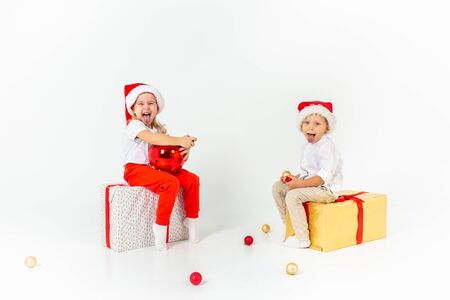 Funny little kids in Santa hat sitting on gift boxes and show their tongues. Isolated on white background. Christmas and new year concept 写真素材