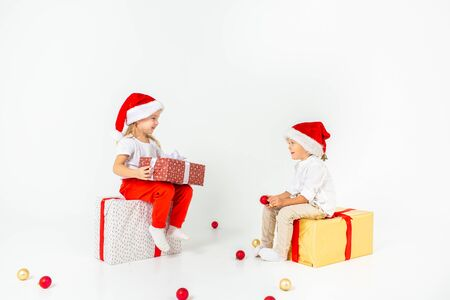 Two funny little kids in Santa hat sitting on gift boxes. Isolated on white background. Christmas and new year concept. 写真素材