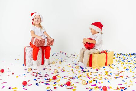 Two funny little kids in Santa hat sitting on gift boxes. Isolated on white background, confetti on a floor.