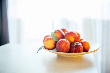 Fresh ripe peaches with leaves on a wooden plate on a kitchen table against the window. Organic food concept and prevention of vitamin deficiency.