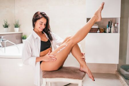 Young slim brunette smiling woman applying body lotion on leg sitting on a chair in a bathroom. Sostnes and skin care concept 写真素材