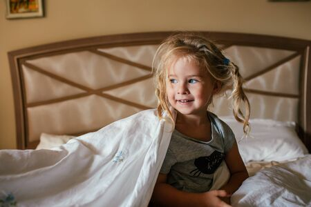 Three years old shaggy white girl sitting on a bed covered with a blanket and smiling.