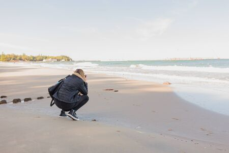 Back view of woman photographing sea with camera or smartphone while standing against copy space sea and sky background. 写真素材