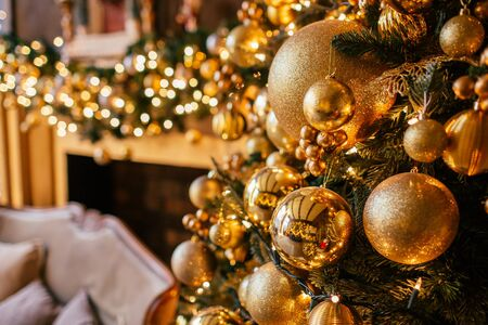 Christmas background with illuminated fir tree with golden decpration and fireplace in living room. Cozy holiday home, close up