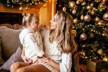 Mother and daughter in white knitting clothes hugging and smiling, winter evening together at home in a decorated living room at Christmas Eve. Family happyness