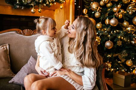 Mother and daughter in white knitting clothes hugging and smiling, winter evening together at home in a decorated living room at Christmas Eve. Family happyness.