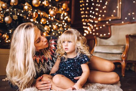 Mother and daughter in shiny clothes hugging and smiling, winter evening together at home in a decorated living room at Christmas Eve. 写真素材