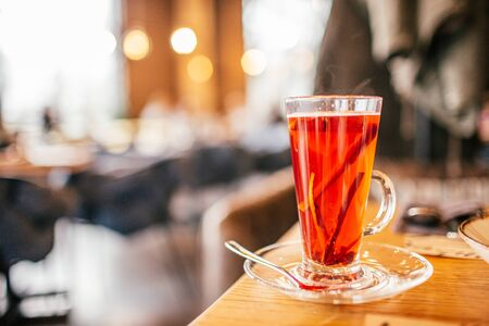 Christmas mulled red wine with spices and oranges on a wooden rustic table at restraunt. Traditional hot drink at Christmas punch