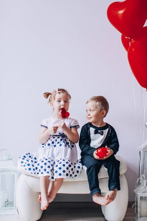 Little girl and boy sitting on a white chair near heart-shaped baloons. Girl licking a red lollipop. Valentines day concept