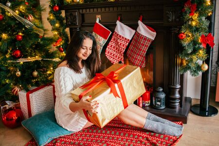 Christmas, winter, happiness concept - smiling woman holding a gift against the background of the Christmas tree and decorated fireplace