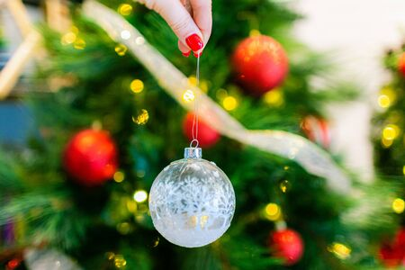 Christmas, decoration, holidays and people concept - close up of woman hand holding christmas ball over living room and tree background