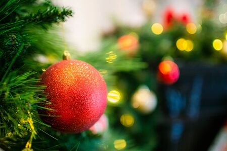 Red glitter Christmas balls on a fir with yellow lights on a background. Copyspace.