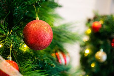 Red glitter Christmas balls on a fir with yellow lights on a background. Copyspace