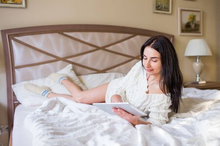 Pretty brunette girl in white knitted dress lying on bed with a tab in and hands and smiling. 写真素材