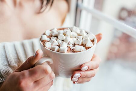 Girl in a white sweater holds a cup of hot chocolate with marshmallows and warms her hands staying near a window. Face is not visible 写真素材