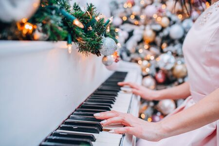 The hand is moving and playing the piano with a backdrop of lights and Christmas trees decorated by Christmas accessories.