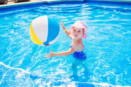 Swimming, summer vacation - lovely smiling girl in pink hat and blue swimsuit playing in blue water with inflatable multicolor ball in a pool