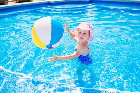 游泳,暑假 - 桃红色帽子和蓝色泳装的可爱的微笑的女孩使用在与可膨胀的多色球的大海在水池