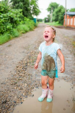 Little blonde girl crying in her dirty clothes after fall into a puddle. Summer, childhood.