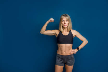 Portrait of beautiful athletic caucasian woman in sport bra and shorts showing biceps of her hand. Blue background. Copy space