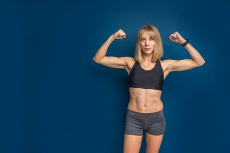 Portrait of beautiful athletic caucasian woman in sport bra and shorts showing biceps of her hand. Blue background. Copy space. Banco de Imagens