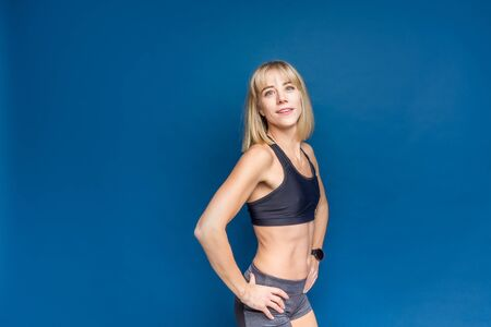 Portrait of beautiful athletic caucasian woman in sport bra and shorts on a blue studio background. Copyspace Banco de Imagens