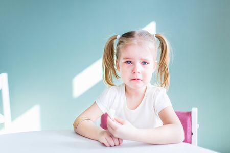 Little blonde girl with two ponytales is crying sitting by the white table with tears on her face. Copyspace