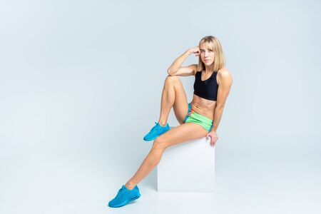 Portrait of beautiful athletic caucasian woman in sport bra and shorts sitting on a white cube on a white studio backgroung. Copyspace