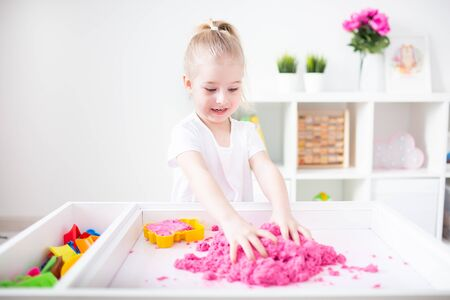 Little blonde girl playing with pink kinetic sand on a white table in a light room. Sensory development. Lessons in a kindergarten