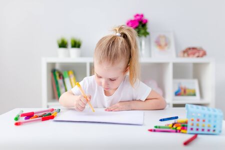 Blonde happy little girl with ponytale drawing and writing lsitting by the white table in light roon. Preschool education, early learning.